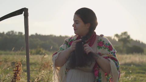 Beautiful overweight woman with a scythe braiding her hair in sunlight on the Footage