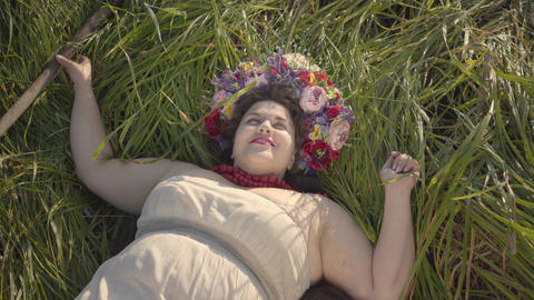 Portrait of carefree overweight woman with a wreath on her head lying on the Live Action