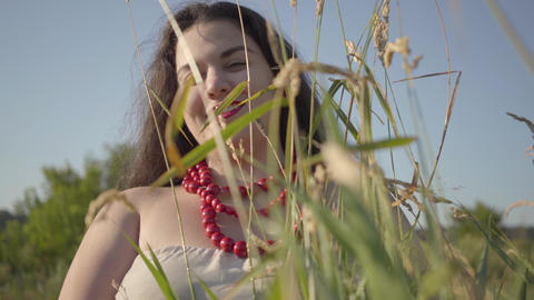 Portrait of carefree plump woman in summer dress necklace looking at the camera Live Action