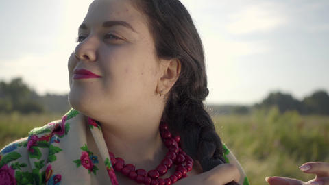 Close-up portrait of beautiful overweight woman braiding her hair in sunlight on Footage