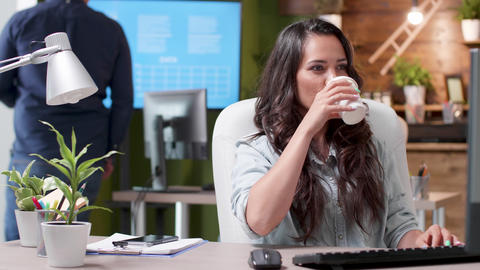 Female manager sipps coffee while working in a busy office Footage