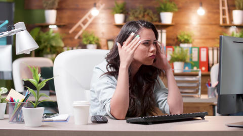 Stressed woman having a headache while working in the office Footage