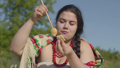 Portrait of beautiful overweight woman eating pancakes with honey outdoors Footage