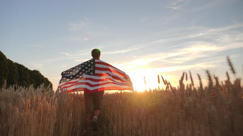 Man walk with the flag of America in the field Footage