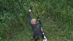 Gardener cutting grass gasoline lawn trimmer in garden. Zoom in Footage