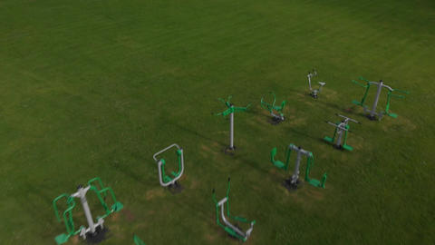 Pullback over outdoor exercise equipment in a field (V454) Footage