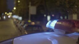 A flashing light on a police car at night ビデオ