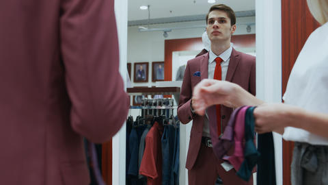 Male dressed in elegant red suit looks at the mirror and chooses his tie Footage