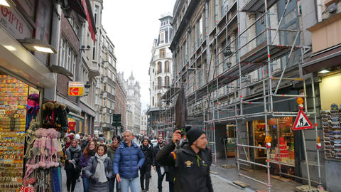 Tourist guide with a group of tourists on the old street in Brussels Live Action