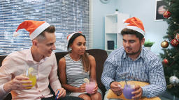 Close up of three friends in Santa hats making cheers and blowing party whistles Footage