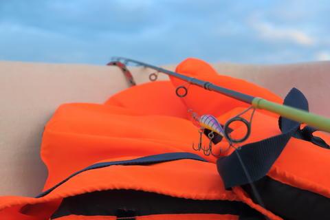 orange life jacket fishing and rod on fishing Photo