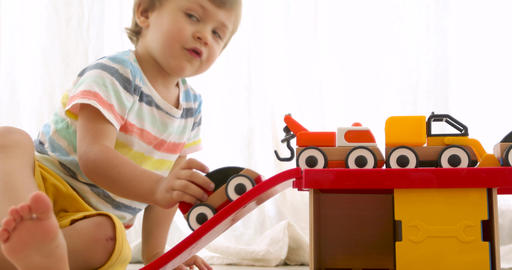 Three years old child boy play with wooden toy cars Footage