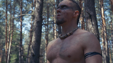 Close up of an ancient warrior with black face paint on his face, in the forest Live Action