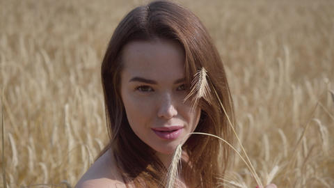 Portrait charming young woman enjoying nature and sunlight in wheat field at Footage