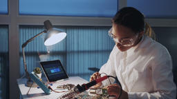 Middle close up of female engineer of electronics in white coat and protective Footage