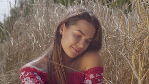 Young carefree woman enjoying nature and sunlight in wheat field at incredible Footage