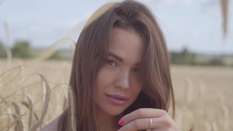 Portrait sweet pretty young woman enjoying nature and sunlight in wheat field at Footage