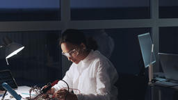 Middle close up of african american engineer making tests on motherboard in lab Live Action