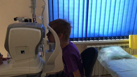 boy checks eyesight in an eye clinic Live Action