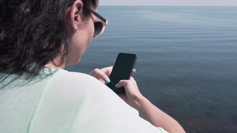 Woman In Sunglasses Using Smartphone Standing On Beach Near Sea Footage