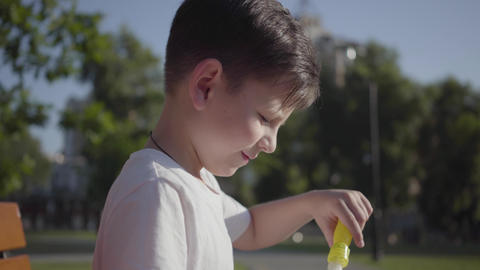 Portrait of cute little boy blowing soap bubbles. Cute child spending time alone Footage