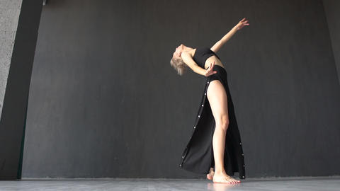 Slim blonde girl doing cartwheel while dancing artistically in studio in slo-mo Live Action