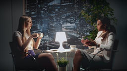 Two young business women speaking about something at the table with a cup of Footage