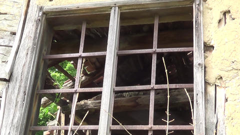 The old broken window with bars on the old cottage Live Action
