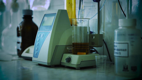 Analysis of oil or dark lager beer. Research lab assorted glassware equipment Live Action