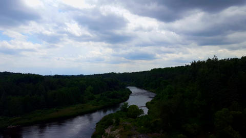 High Angle View of Calm Flowing River Surrounded By Lush Green Forests Under Cloudy Overcast Sky Footage