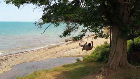 Man swinging on rope swing under tree on green hill above deserted beach. Calm azure sea and Footage