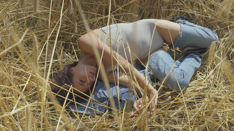 Graceful woman wearing bodysuit with short hair lying on the wheat field. Girl Footage
