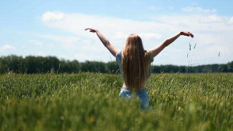 Cute girl walking on green field with open arms Footage