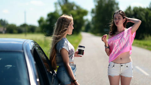 Young women eating and drinking coffee near car Footage