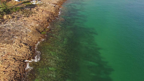 Beautiful emerald ocean wave on a rocky beach aerial view Footage