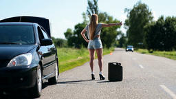 Beautiful girl hitchhiking on rural road back view Footage