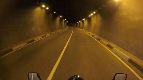 motorcycle road trip, towards adventures, riding through dark gloomy tunnel Live Action