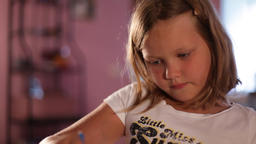 little girl blonde draws with pencils.blurred background Live Action