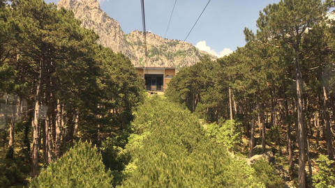 View from window moving cable car cabin among forest trees in mountain. Cable Live Action