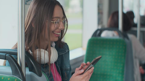 Young stylish woman using public transport, sitting with phone and headphones in Live Action
