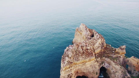 Seagulls over rocks in the ocean aerial view Footage