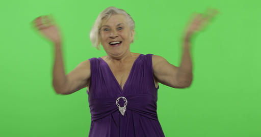 An elderly woman shows amazement, joy and smiles. Old grandmother. Chroma key Footage