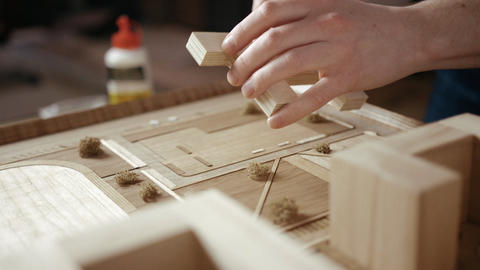 Craftsman Arranges Buildings on a Wooden Architectural Layout Live Action