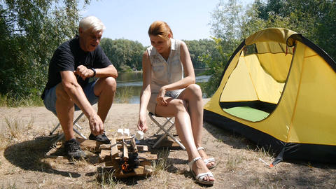 A man and a girl roasting marshmallows on a fire. Hiking, travel, green tourism Live Action