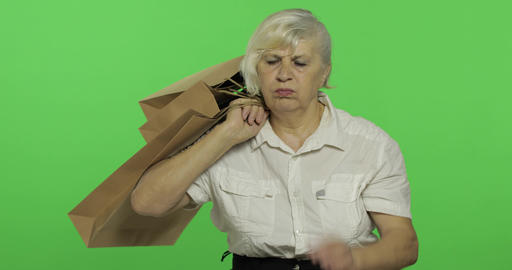 An elderly bored woman with shopping bags. Shopping. Presents. Chroma key Footage