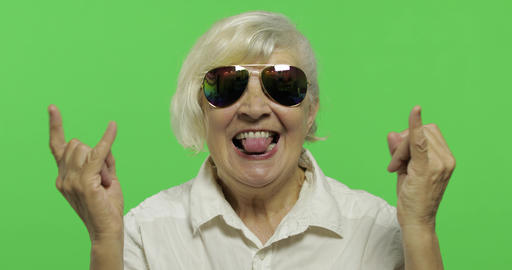 An elderly woman show sign of the horns with her hands and showing tongue Live Action