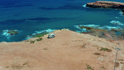 Aerial view. Camper van on a parking lot on a rock near the sea. RV park Live Action