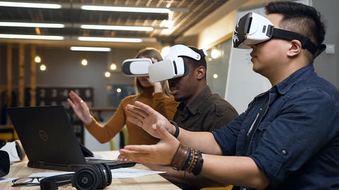 Three multi ethnic worker working with vr virtual reality glasses in the modern Live Action