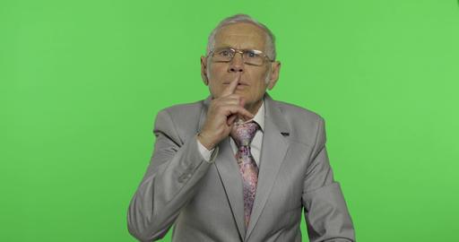 Elderly businessman showing silence gesture. Senior man showing shh gesture Live Action