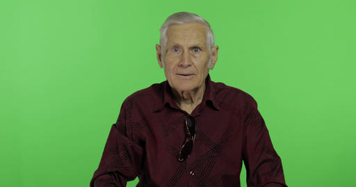 Senior man hides his face at his hands and spying. Handsome old man. Chroma key Footage